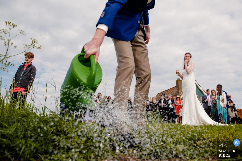 De net geplante boom ter ere van de bruiloft wordt nog even water gegeven op het eiland Pampus nabij Amsterdam. De bruid en familie kijken toe met een glaasje champagne.