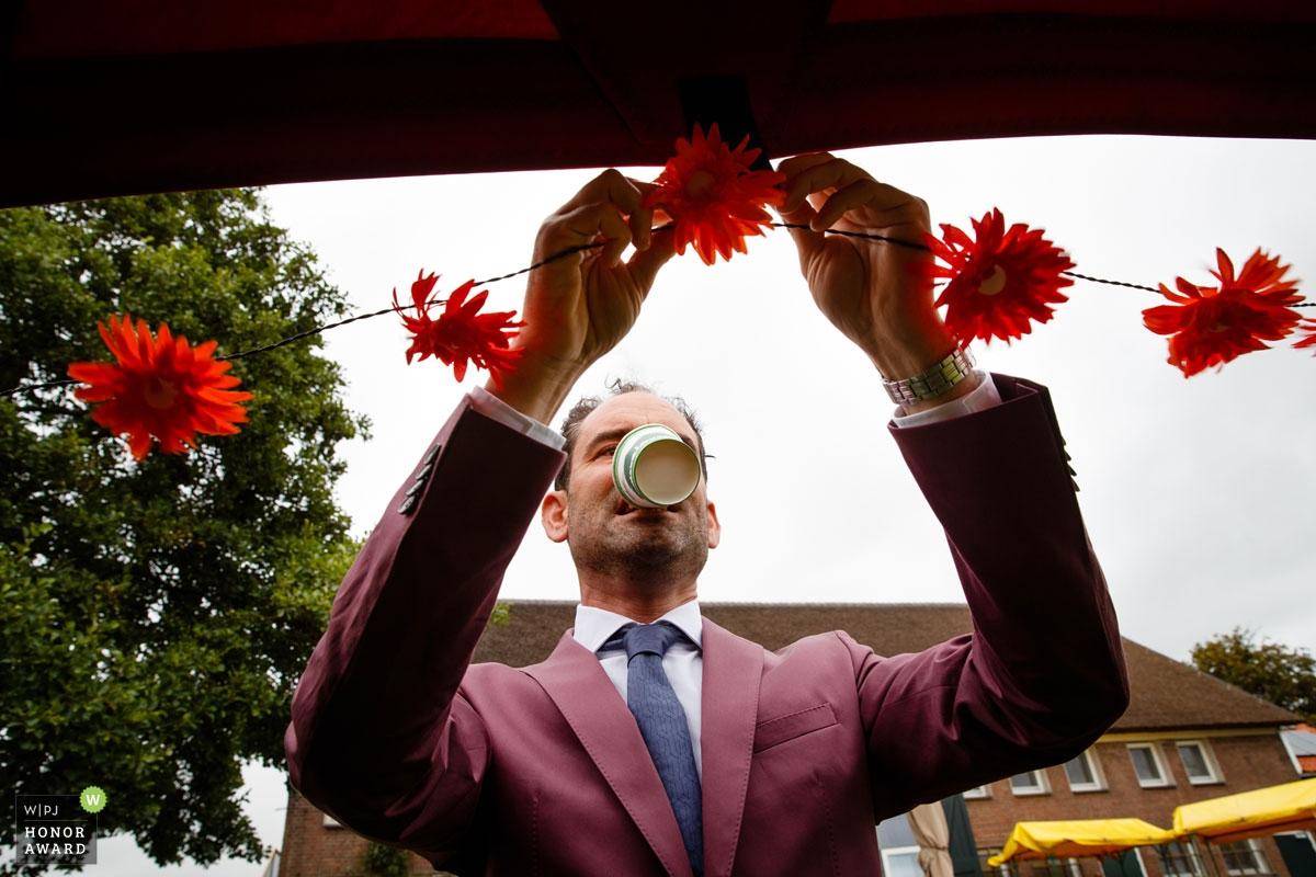 Nog even een laatste lampjes-bloem slinger ophangen en koffie drinken zonder handen. De bruidegom draagt zijn steentje bij aan de voorbereidingen.