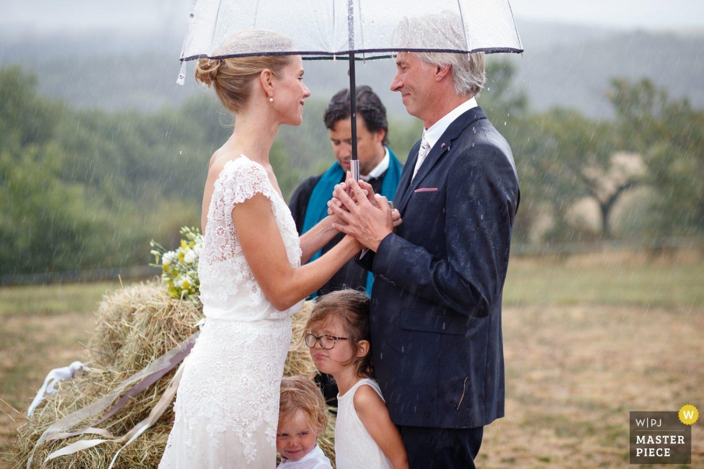 Tijdens een hevige regenbui in Frankrijk geven bruid en bruidegom elkaar het jawoord onder een transparante paraplu terwijl de kinderen tussen hun in schuilen.