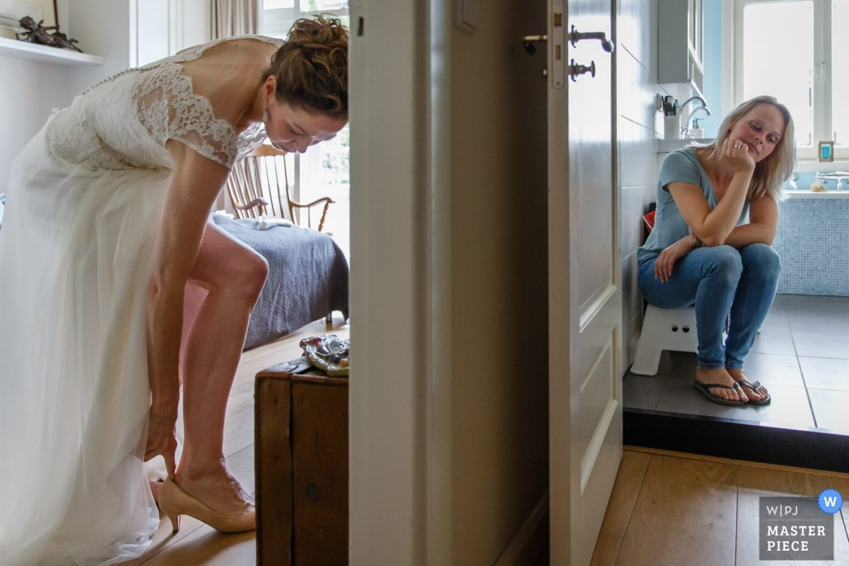 De bruid trekt haar schoen aan in de ene kamer terwijl de make up artiest even uitrust in de badkamer.