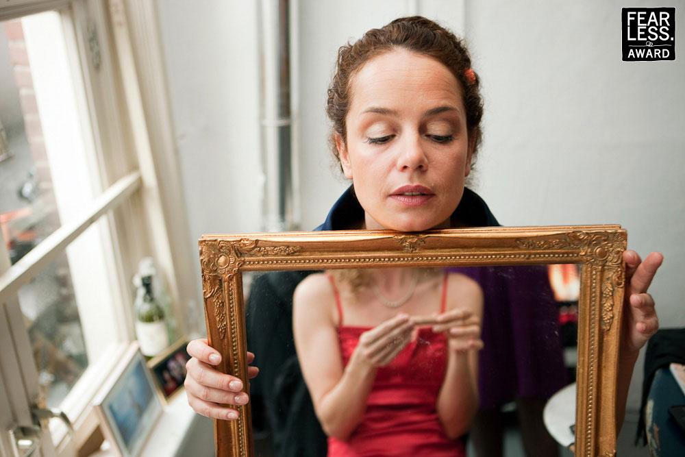 Een spiegel met een reflectie van de ene vrouw terwijl het hoofd van de vrouw die de spiegel vasthoud te zien is. Samen een vervreemdend beeld.