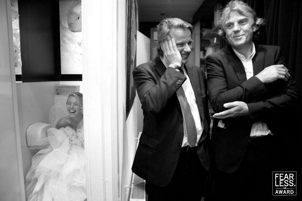 De bruid in het wit moest naar de wc maar de jurk was zo groot dat de deur niet dicht kon. Twee mannen in het zwart op de gang lijken er niets van te willen zien.