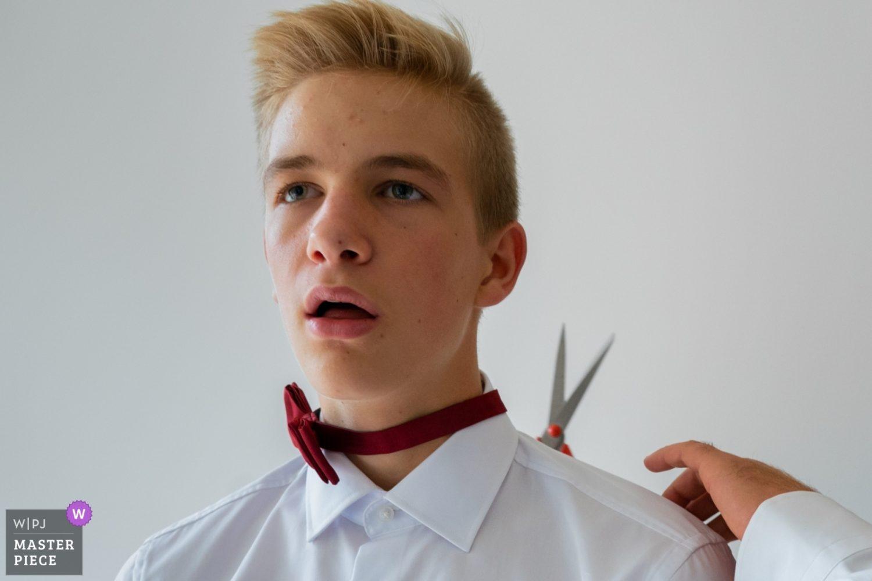 De zoon van de bruidegom wordt nog even geholpen met zijn strik - er moet geknipt worden.