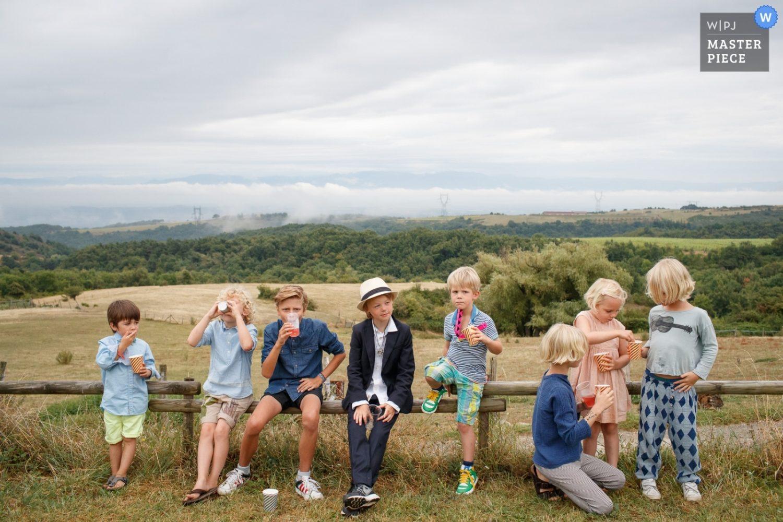Vlak voor de ceremonie op een camping in Frankrijk genieten de kinderen nog even van hun drankje. Allemaal in hun camping-beste kleren.